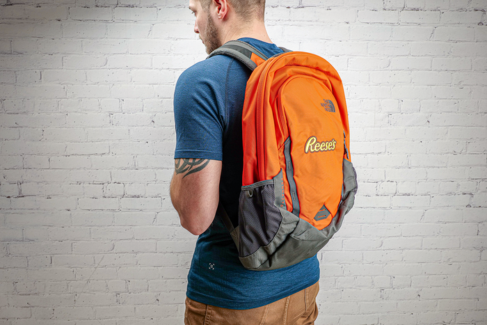 Image of Orange North Face Back Pack with the REESE'S Logo Packaging